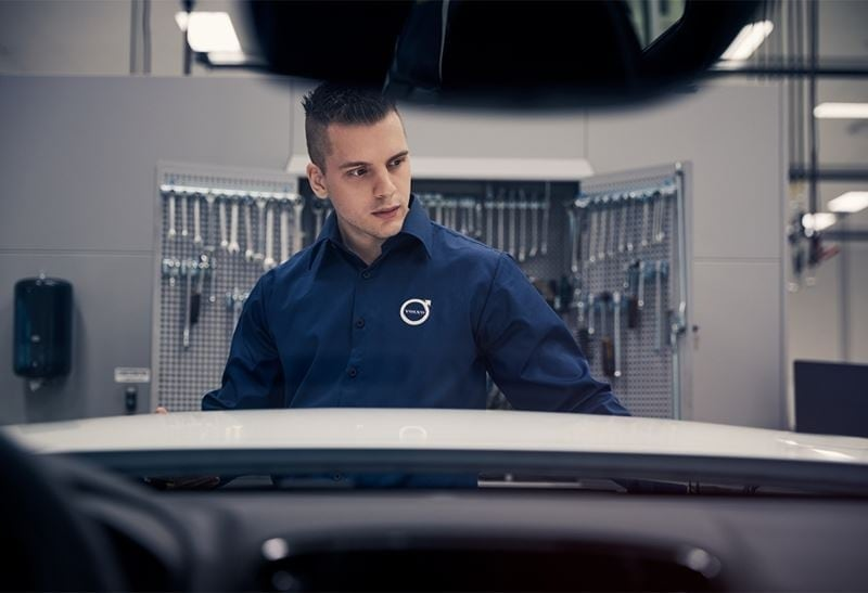 A man wearing a Volvo technicians suit